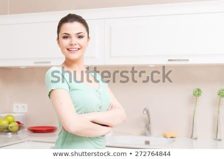 Smiling woman standing up in her kitchen stock photo © wavebreak_media