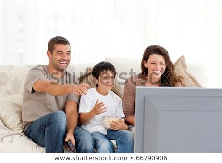 Család nevet néz televízió együtt élet Stock fotó © HASLOO