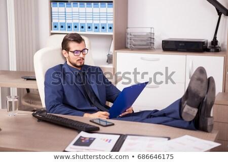 homem · inclinando-se · para · trás · cadeira · sorridente · negócio · escritório - foto stock © rugdal