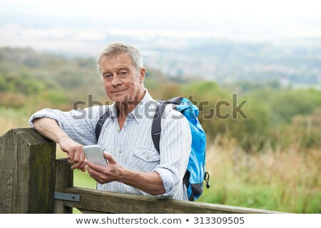 Senior Man Checking Location With Mobile Phone On Hike Stock photo © HighwayStarz