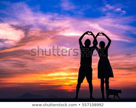 Woman's silhouette making the heart gesture Stock photo © konradbak
