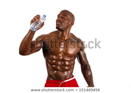beautiful and muscular man drinking water in dark background stock photo © nenetus