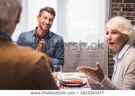 Pleased senior man talking and pointing Stock photo © ozgur