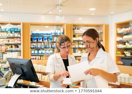 Team of pharmacists in drug store checking pharmaceuticals Stock photo © Kzenon