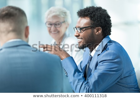 Elderly business man by the table with partners Stock photo © deandrobot