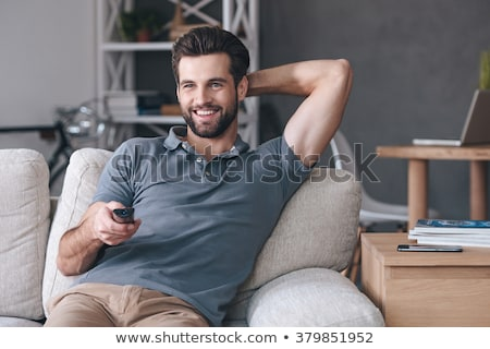Young man holding remote control while watching TV Stock photo © deandrobot