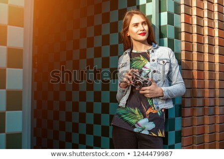 Beautiful young woman photographer walking on the street Stock photo © deandrobot