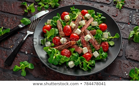 Pork meat grilled with fresh vegetable salad on a white plate. t Stock photo © Yatsenko