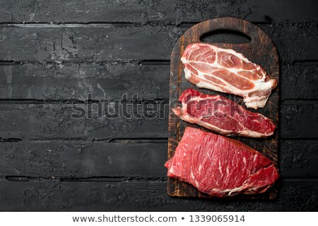 Fresh raw pork tenderloin, chopped meat on dark wooden rustic background, top view Stock photo © yelenayemchuk