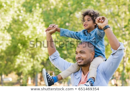 Stock photo: Dad carrying son on his shoulders.