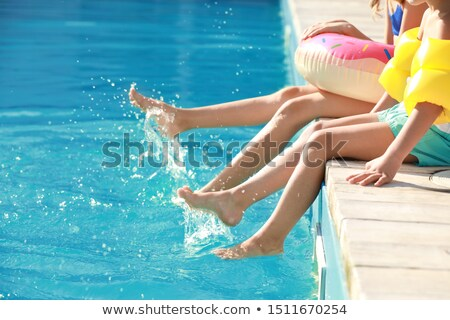 friends sitting at edge of pool stock photo © is2