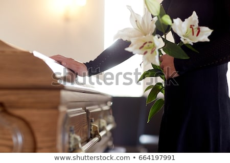 woman with lily flowers and coffin at funeral Stock photo © dolgachov