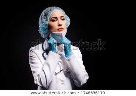 Female surgeon takes off protective surgical mask after operatio Stock photo © stevanovicigor