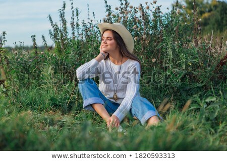 Woman with cowboy hat sitting in meadow Stock photo © IS2