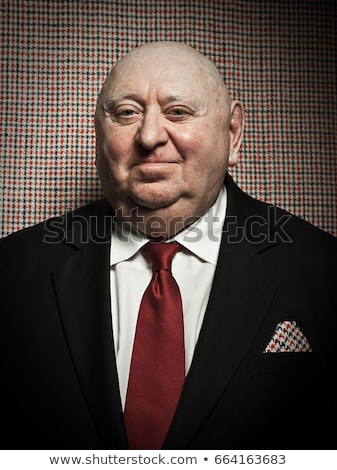 Senior man against dogtooth check background, with matching handkerchief Stock photo © IS2