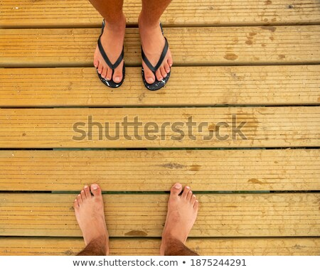 Legs on the old pier on the background of the sea Stock photo © galitskaya