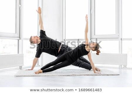 Couple performing yoga pose Stock photo © Kzenon