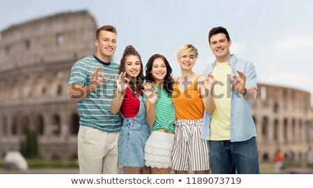 happy friends showing ok hand sign over coliseum Stock photo © dolgachov
