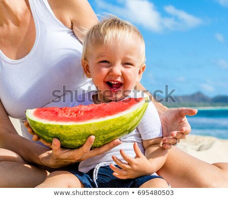 Happy family mother and son eating a watermelon on the beach. Children eat healthy food Photo stock © galitskaya