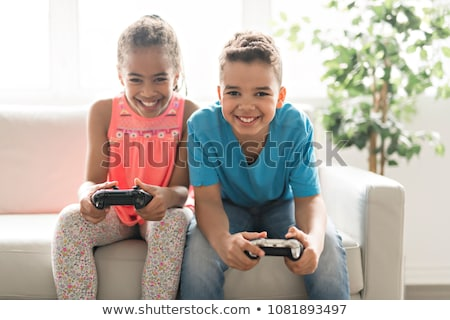 Foto stock: black boy play video game on sofa with headset