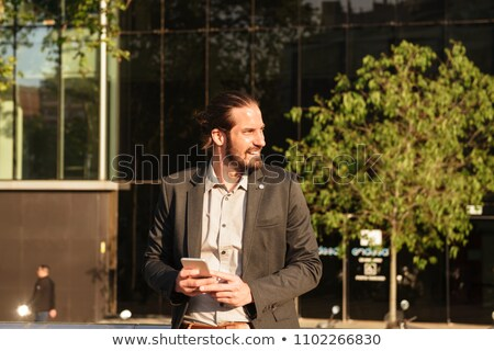 Image of bearded businessman 30s in formal suit holding smartpho Stock photo © deandrobot