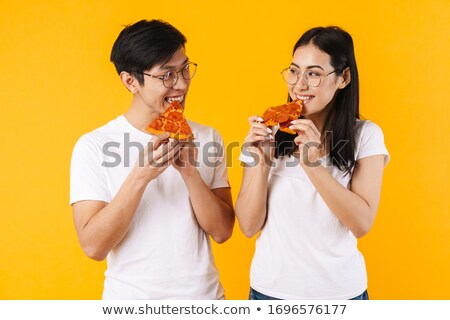 portrait of a satisfied young asian man eating pizza stock photo © deandrobot