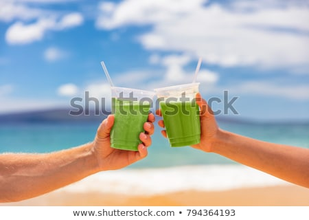couple toasting the juice glasses on beach stock photo © andreypopov