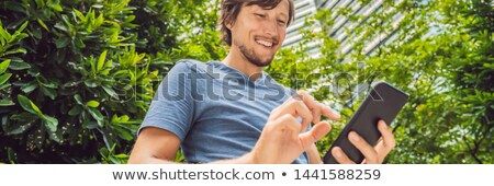 Stockfoto: Man Tourist Using Navigation App On The Mobile Phone Navigation Map On A Smartphone In A Big City