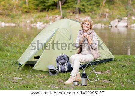 Mature smiling woman holding hot drink while sitting on small tourist chair Stock photo © pressmaster