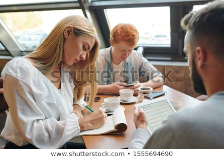 Two casual guys using gadgets while blonde girl making notes in notepad in cafe Stock photo © pressmaster