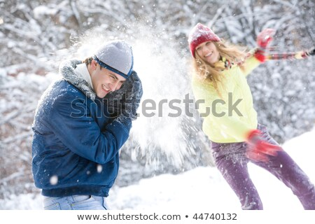 Woman throwing snowball on her guy in winter in playful mood Stock photo © Kzenon