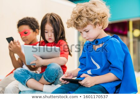 Adorable blonde boy in costume of superman scrolling in smartphone Stock photo © pressmaster
