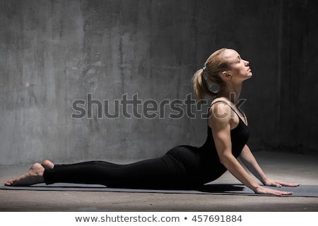 Young woman practicing yoga, doing cobra Pose on dark background Stock photo © GVS
