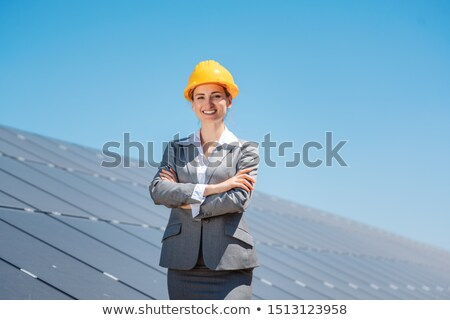 Woman investor in clean energy standing in front of solar panels Stock photo © Kzenon