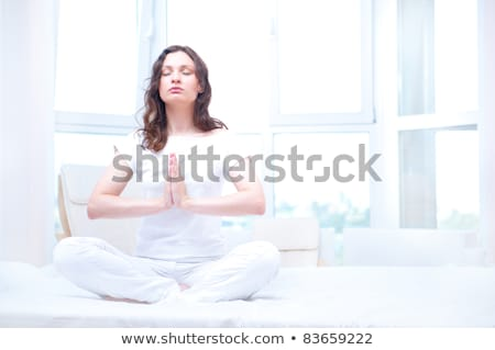 Young woman meditating with closed eyes in bright bedroom sittin Stock photo © HASLOO
