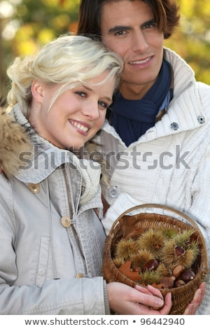 couple dressed in warm clothes,  woman is holding a wickerwork basket full of chestnuts Stock photo © photography33