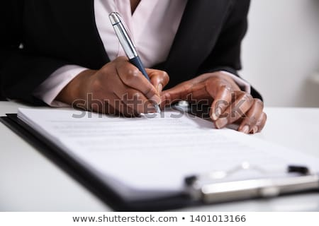 African employee writing on clipboard Stock photo © stockyimages