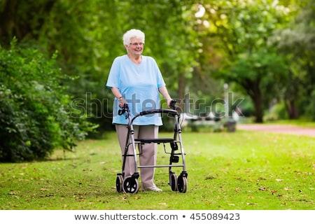 senior · dame · jonge · vrouw · holding · handen · rolstoel · buiten - stockfoto © melpomene