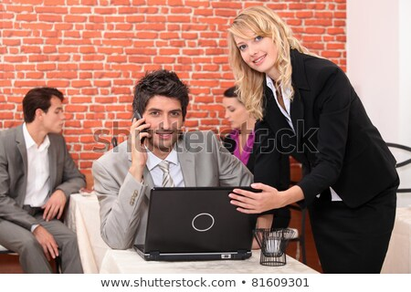 Waitress in a restaurant helping a man with his laptop computer Stock photo © photography33