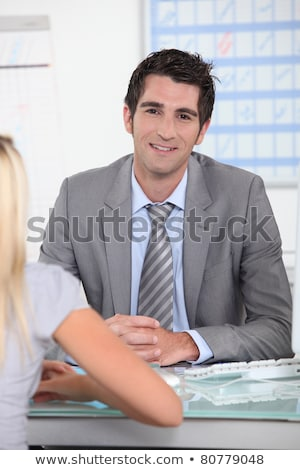 Man in suit sitting across a desk from a young woman with a schedule in the background Stock photo © photography33
