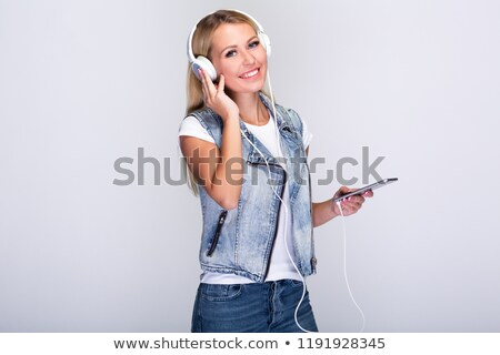 Beautiful woman using her headphones while standing against a white background stock photo © wavebreak_media