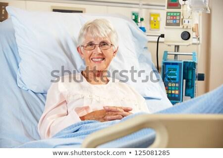 Smiling nurse looking at a female patient in hospital ward stock photo © wavebreak_media