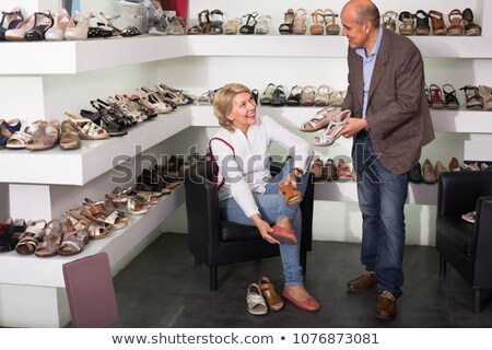 Woman is sitting in a boutique trying shoes and smiling  Stock photo © wavebreak_media