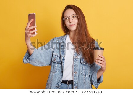 pretty young woman sending message by cellphone stock photo © pablocalvog