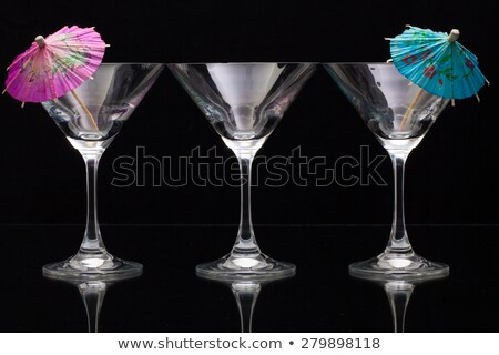 Three empty glasses of champagne with paper umbrellas Stock photo © CaptureLight