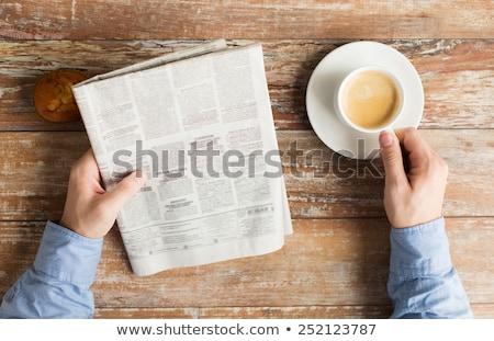 businessman reading newspaper and drinking coffee in office stock photo © deandrobot