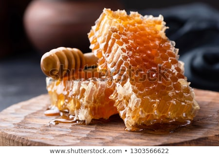 Honey dripping on honeycombs on wooden background Stock photo © mady70