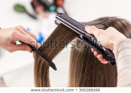 Close-up of a hairdresser straightening long brown hair with hair irons. stock photo © pixinoo