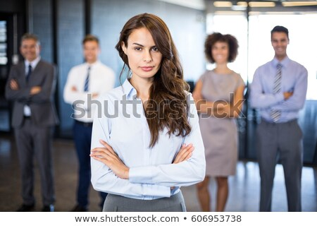 confident young businesswoman standing with her arm crossed stock photo © mmarcol