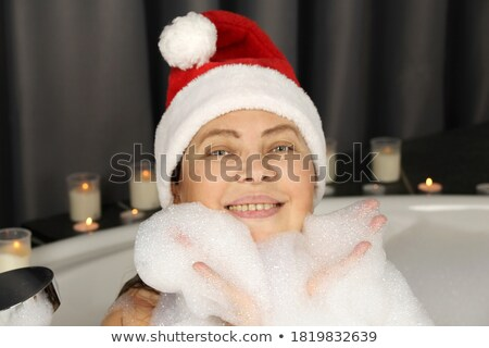 Cheerful woman sitting and laughing in bathtub with foam Stock photo © deandrobot